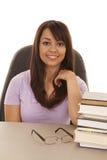 Donna allo scrittorio con una pila di sorridere dei libri Fotografia Stock Libera da Diritti