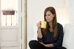 Donna allo strato moderno della casa del salone dell'appartamento che gode della tazza di tè del caffè Immagine Stock Libera da Diritti