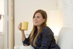 Donna allo strato moderno della casa del salone dell'appartamento che gode della tazza di tè del caffè Fotografia Stock