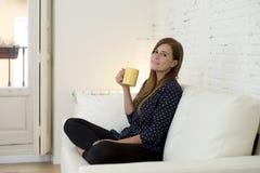 Donna allo strato moderno della casa del salone dell'appartamento che gode della tazza di tè del caffè Fotografie Stock Libere da Diritti