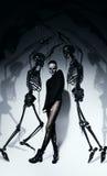 Donna alta nel nero con gli scheletri neri Fotografia Stock