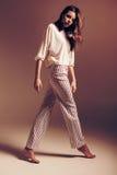 Donna alta in pantaloni a strisce e nella cima bianca Fotografie Stock Libere da Diritti
