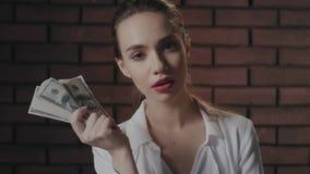 Donna altera che guarda alla macchina fotografica e che mostra la pila dei soldi alla macchina fotografica sul muro di mattoni archivi video