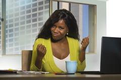 Donna americana di affari dell'africano nero che sorride lavoro allegro e sicuro allo scrittorio del computer che celebra promoti immagini stock