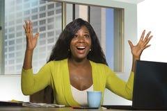 Donna americana di affari dell'africano nero che sorride lavoro allegro e sicuro allo scrittorio del computer che celebra promoti immagine stock