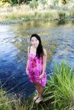Donna americana giapponese attraente che sta sulla sponda del fiume Fotografie Stock Libere da Diritti