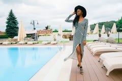 Donna americana in vestito lungo in bande e black hat attraenti, graziosi, teneri, bei Camminata di modello vicino allo stagno di Fotografie Stock Libere da Diritti