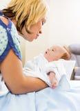 Donna amorosa che esamina Babygirl sveglio in ospedale Immagini Stock