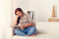 Donna annoiata che legge un libro sullo strato a casa Fotografia Stock Libera da Diritti