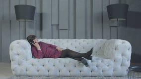 Donna annoiata che parla sul telefono che si trova sul sof? a casa