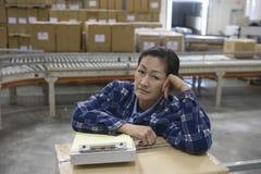 Donna annoiata con la lavagna per appunti nel magazzino di distribuzione immagini stock libere da diritti