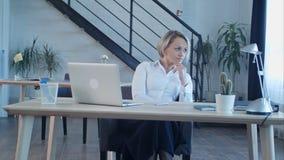 Donna annoiata infelice che si siede nell'ufficio Fotografie Stock Libere da Diritti