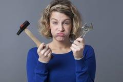 Donna annoiata 20s che ha disinteresse per il lavoro manuale dei meccanici o DIY Fotografia Stock