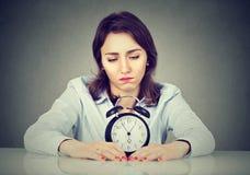 Donna annoiata triste con la sveglia che si siede alla tavola nel suo ufficio Immagini Stock