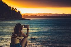 Donna anonima che prende immagine del tramonto fotografia stock