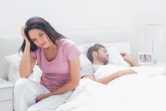 Donna ansiosa che pensa mentre si siede nel suo letto fotografie stock