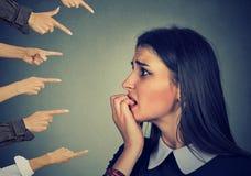 Donna ansiosa giudicata dalle mani differenti Accusa della ragazza colpevole Immagine Stock