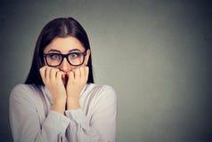 Donna ansiosa incerta che morde le sue unghie che hanno bisogno per qualcosa immagini stock libere da diritti