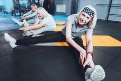 Donna anziana adorabile che allunga durante il corso di formazione Fotografia Stock Libera da Diritti