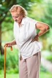 Donna anziana all'aperto con dolore alla schiena fotografia stock
