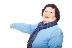 Donna anziana allegra che indica lo spazio della copia Fotografia Stock