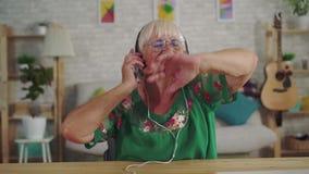 Donna anziana allegra con capelli grigi in cuffie che ascolta la musica e la fine ballante su video d archivio