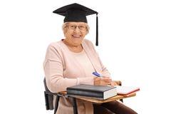 Donna anziana allegra con il cappello di graduazione che si siede nella sedia della scuola Immagine Stock
