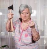 Donna anziana arrabbiata con un'ascia Immagini Stock