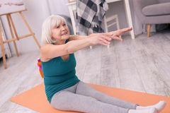 Donna anziana atletica che effettua allungando esercizio Fotografie Stock