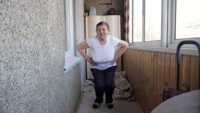 Donna anziana anziana attiva che fa gli esercizi di mattina sulla veranda stock footage