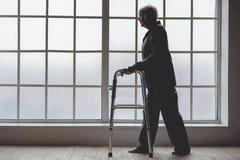 Donna anziana calma che tiene camminatore pieghevole nella sala della clinica fotografie stock