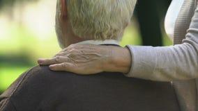 Donna anziana che abbraccia con attenzione il suo marito che si siede sul banco, fiducia di relazione stock footage