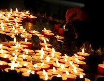 Donna anziana che accende una candela in una chiesa Immagine Stock Libera da Diritti
