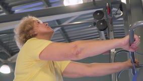 Donna anziana che allunga vicino al simulatore nella palestra archivi video