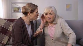 Donna anziana che aspetta di sentire il suo amico senior, problemi con l'udienza, sordità archivi video