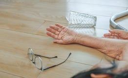 Donna anziana che cade a casa, attacco del focolare immagini stock