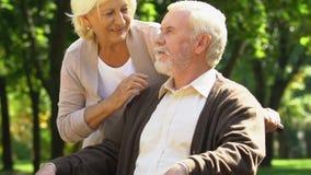 Donna anziana che cammina con il suo uomo handicappato in parco vicino alla casa di cura, supporto stock footage