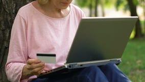 Donna anziana che compera online, facendo uso della carta di credito per pagare l'acquisto, commercio elettronico stock footage