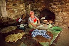 Donna anziana che cucina il forno di pietra rustico del piatto tradizionale di Gozleme di vecchio villaggio turco Immagine Stock