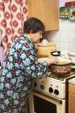Donna anziana che cucina minestra sulla stufa Fotografia Stock
