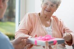 Donna anziana che dà presente immagini stock