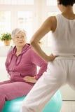 Donna anziana che esamina addestratore personale Fotografia Stock