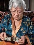 Donna anziana che esamina 100 cento banconote in dollari lacerata Immagini Stock Libere da Diritti
