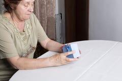 Donna anziana che esamina il contenitore di regalo che accetta presente fotografie stock