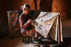 Donna anziana che fa batik tradizionale Fotografia Stock