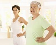 Donna anziana che fa le esercitazioni con l'addestratore Fotografia Stock Libera da Diritti