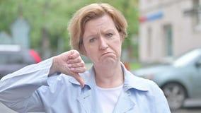 Donna anziana che Gesturing i pollici giù stare all'aperto stock footage