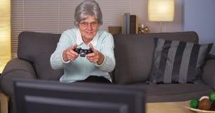 Donna anziana che gioca i videogiochi Fotografia Stock