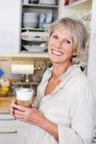 Donna anziana che gode di una tazza di cappuccino immagini stock