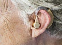 Donna anziana che indossa una protesi acustica fotografia stock libera da diritti